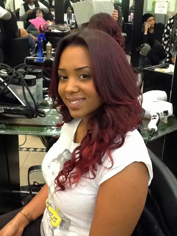 cliente sorride a seguito di un taglio di capelli con meches rosse nelle punte
