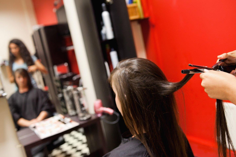 cliente in fronte allo specchio mentre la parrucchiera piastra i suoi capelli