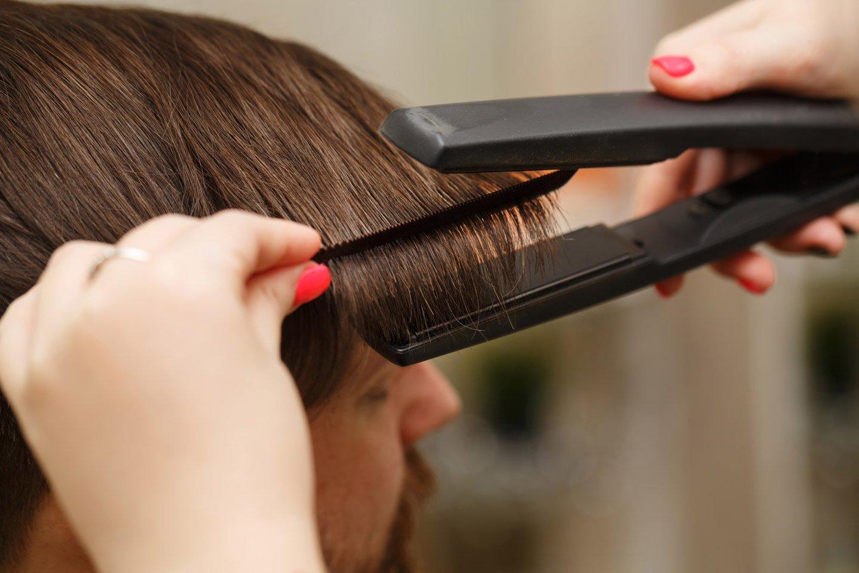 parrucchiera usa una piastra per capelli su un uomo