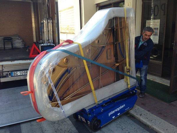 Un uomo trasporta un pianoforte imballato