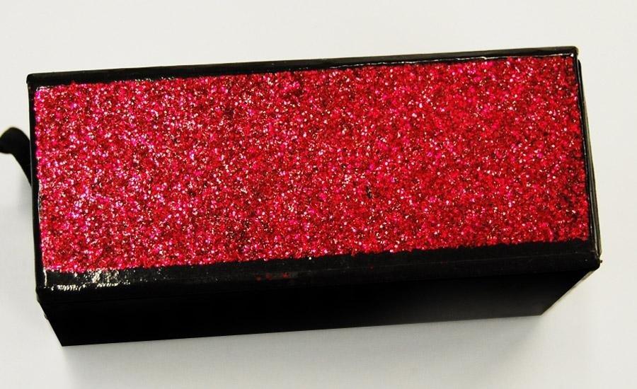 Glitter applicato Applicazione glitter rosso su carta plastificata lucida