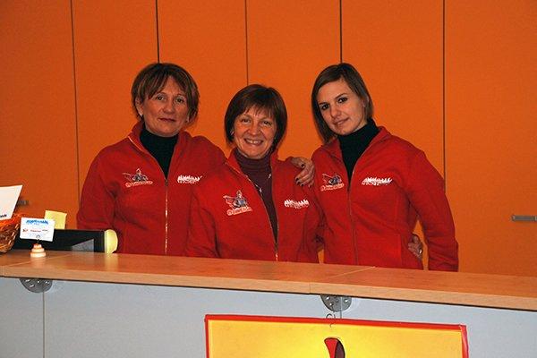 tre donne con una divisa rossa in posa per una foto