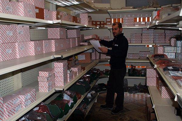 un uomo con in mano un foglio in un magazzino di ricambi