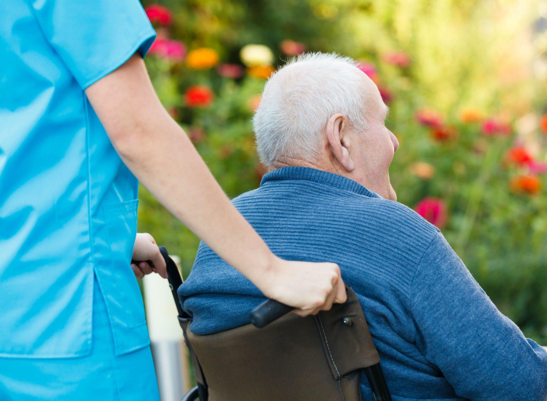infermiera spinge carrozzina con anziano signore