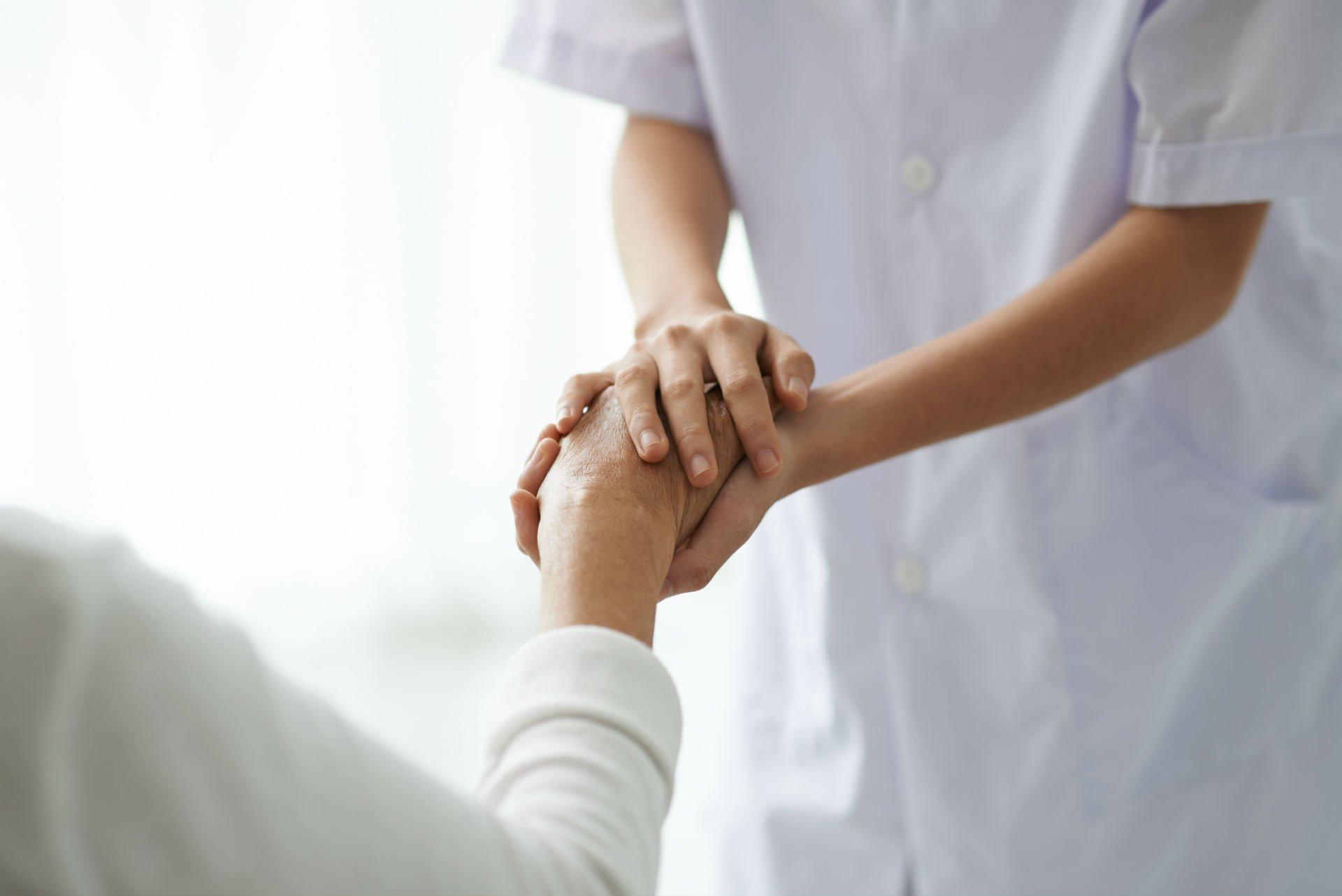 un'infermiera che tiene per mano un'anziana signora