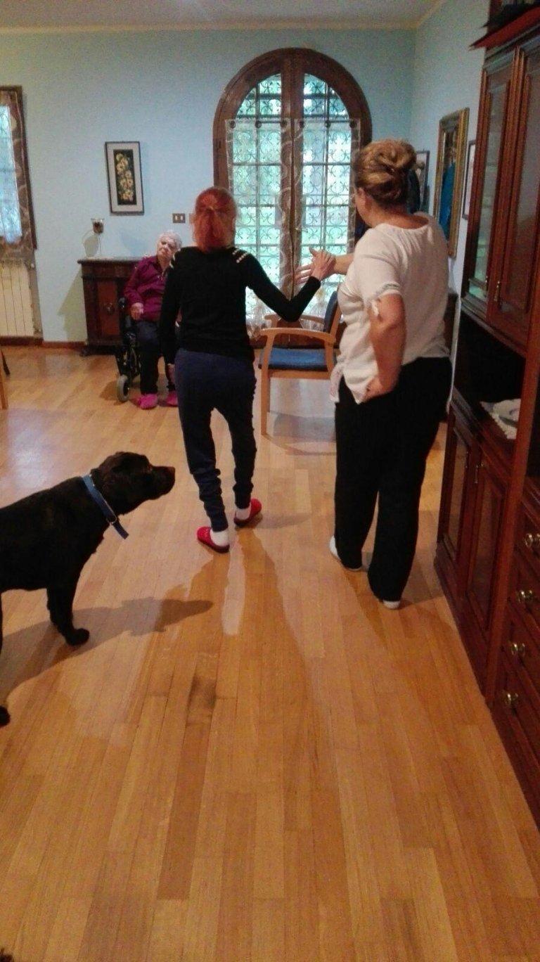 un'anziana signora che viene accompagnata da una donna e un cane nero