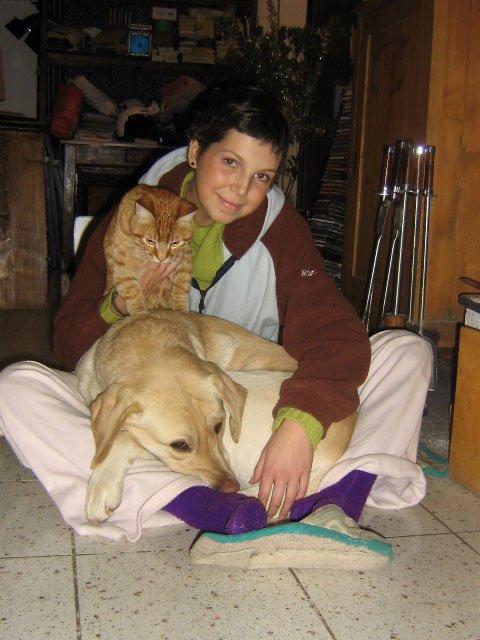 una ragazza seduta a terra con un cane e un gatto