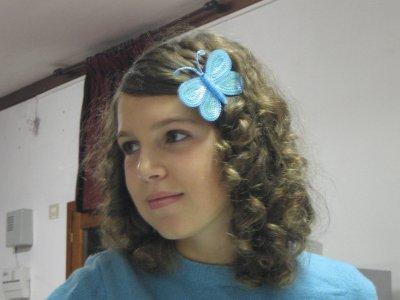 una bambina con capelli castani ricci con una molletta azzurra a forma di farfalla