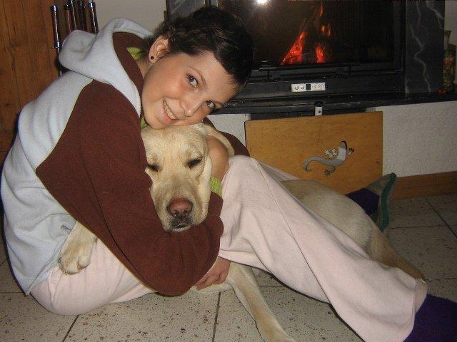 una ragazza seduta e abbracciata a un cane vicino a una stufa