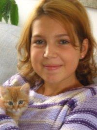 una ragazza con capelli arancioni con in braccio un gattino