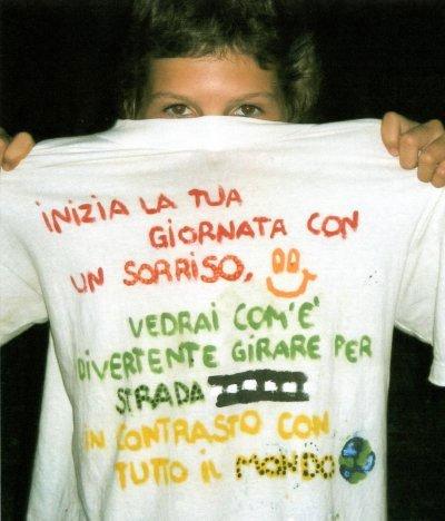 una ragazza che mostra una maglietta con scritto inizia la tua giornata con un sorriso, vedrai com'è' divertente girare per strada in contrasto con tutto il mondo
