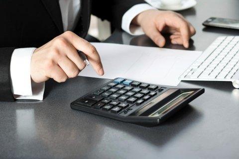 Uomo di fronte al computer e usando una calcolatrice
