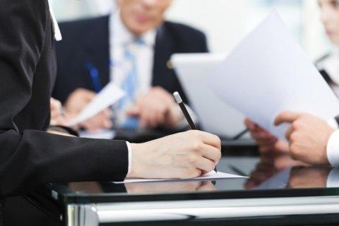 Alcuni uomini in una riunione prendendo note