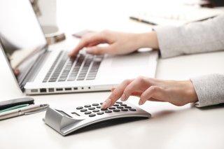 Donna lavorando a due mani,usando il computer e la calcolatrice