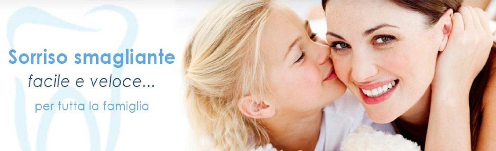 una bambina che bacia la mamma mentre sorride
