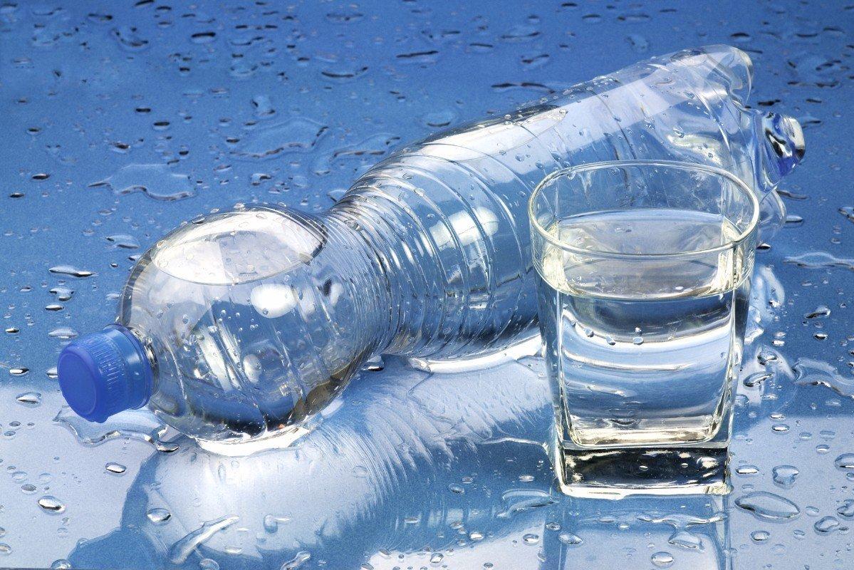 Una bottiglia d'acqua giacente e un bicchiere pieno d'acqua su una superficie piena di gocce