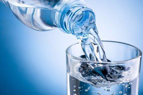 Una bottiglia riempiendo un bicchiere d'acqua