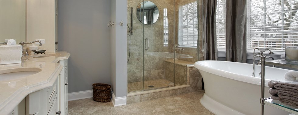 A stylish bathroom with a rolltop bath and glass shower