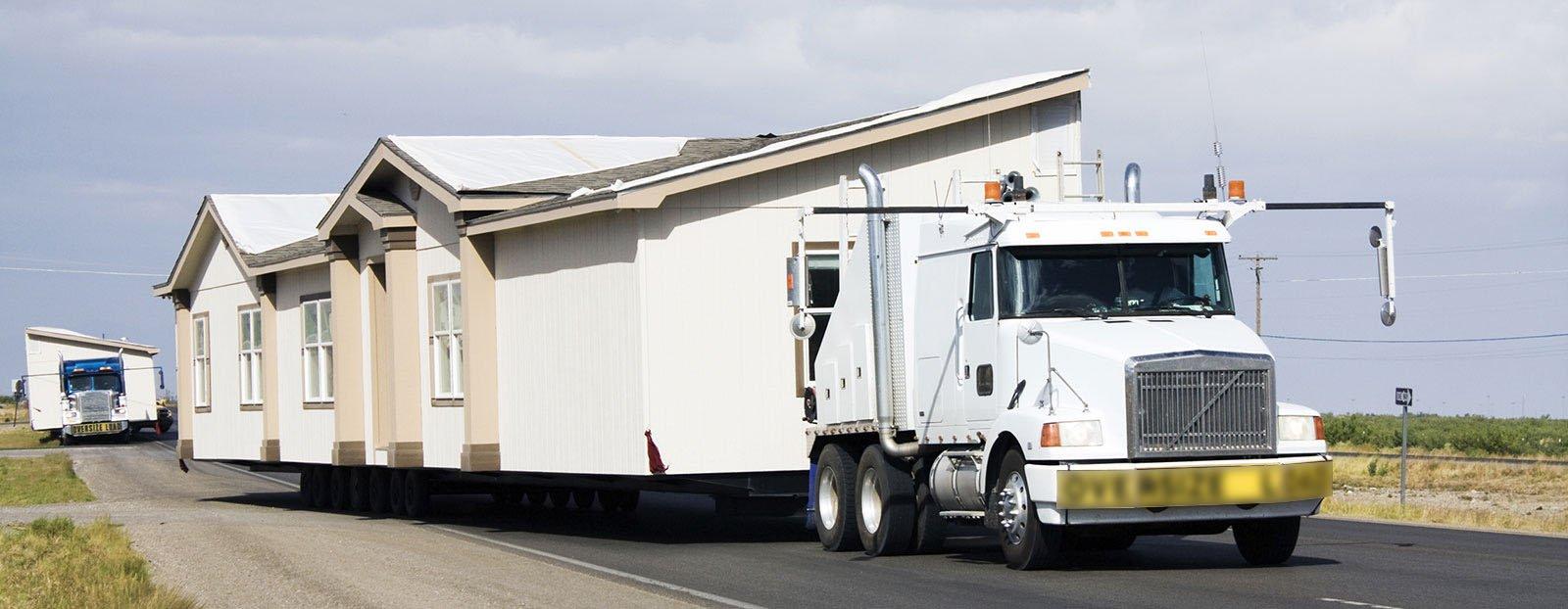 un camion bianco che trasporta una casa
