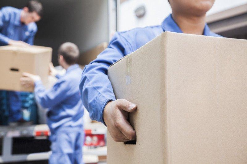 delle persone che scaricano degli scatoloni da un camion