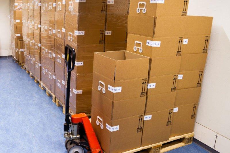 degli scatoloni sopra un trespalle e altri sopra a dei bancali