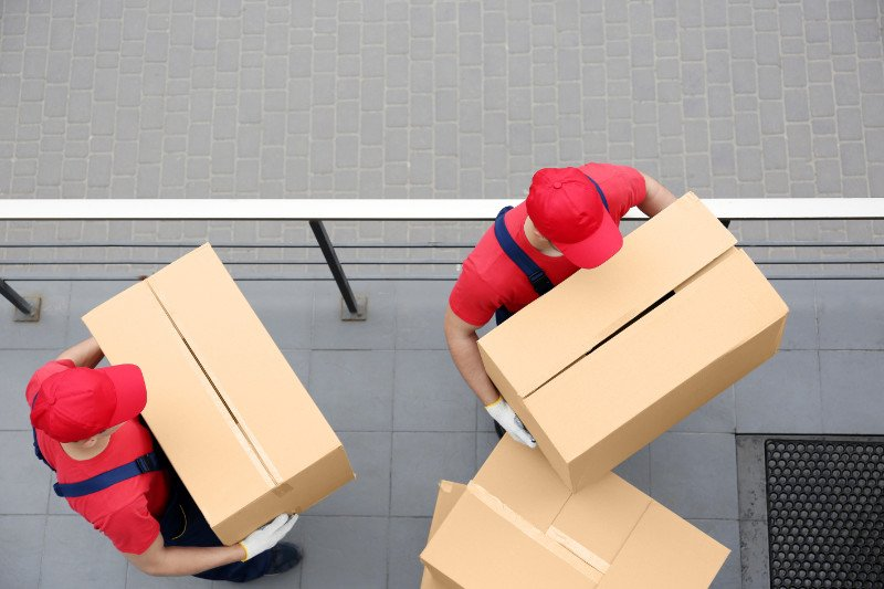 degli uomini con degli scatoloni in mano