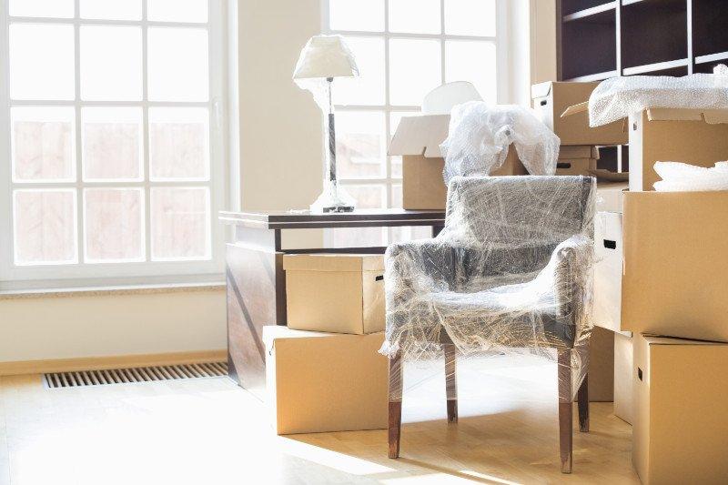 una sedia con della plastica, degli scatoloni e un tavolino con sopra una lampada