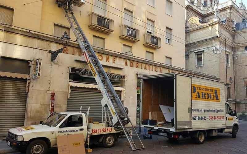 una scala estensibile da traslochi, un camion e un altro mezzo vicino a un condominio in città