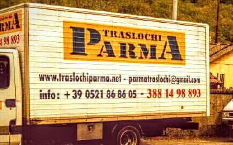 il rimorchio di un camion da traslochi con scritto Traslochi Parma e delle informazioni di contatto