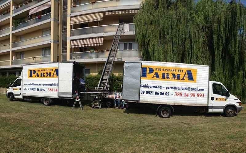 due camion dei traslochi parcheggiati in un prato con un albero e una scala estensibile che arriva al balcone di un condominio