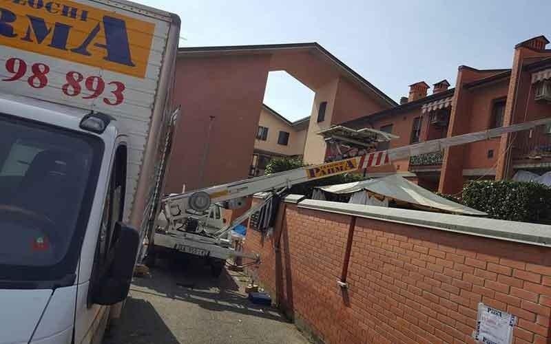 un camion con un braccio estensibile che arriva vicino a un condominio e sulla sinistra un altro camion parcheggiato