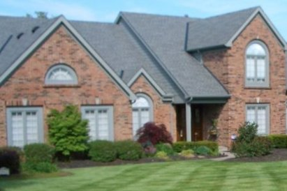 brick house with large, fresh cut lawn