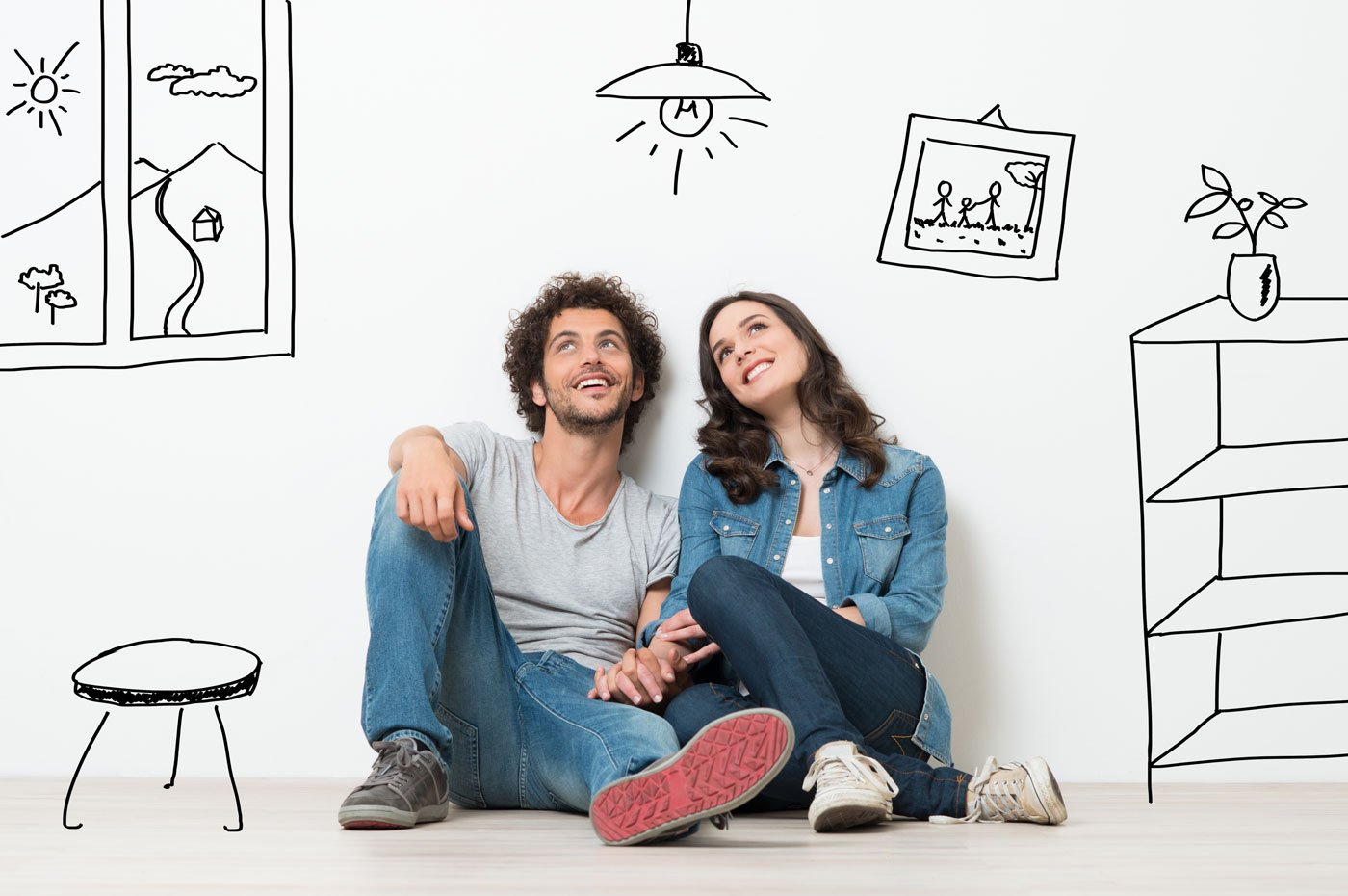 Happy Young Couple Sitting On floor dreaming their new home
