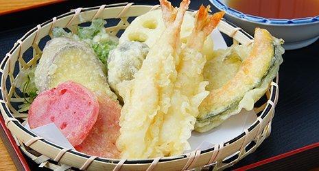 Un cestino di paglia con delle verdure e gamberi fritti in pastella