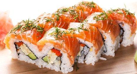 Un tagliere di sushi con fette di salmone e aromi