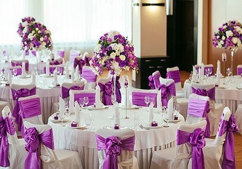 dei tavoli decorati con i fiori di color viola per una cerimonia