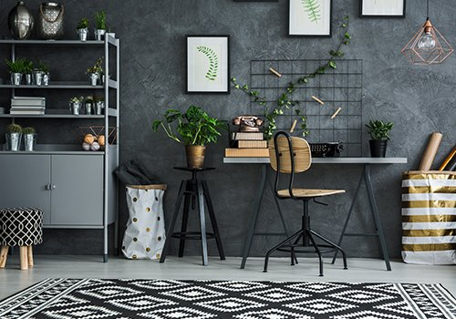 una scrivania con un vaso di una pianta rampicante