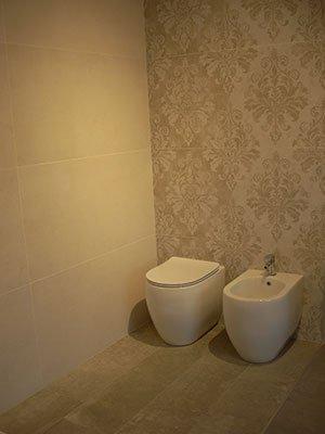 un bagno con i sanitari e dei muri con carta da parati