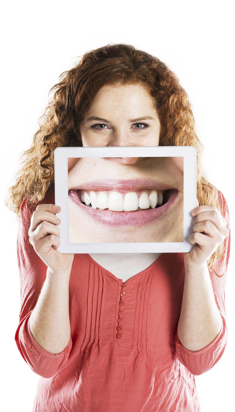 girl holding up ipad with huge smile showing white teeth
