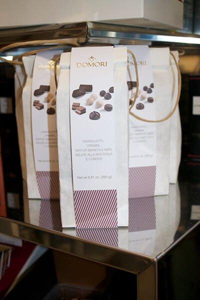scatole di cioccolatini Domori posizionate su un piano di vetro