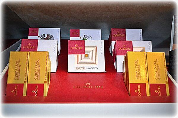 scatole di cioccolato Domori su un piano rosso obliquo