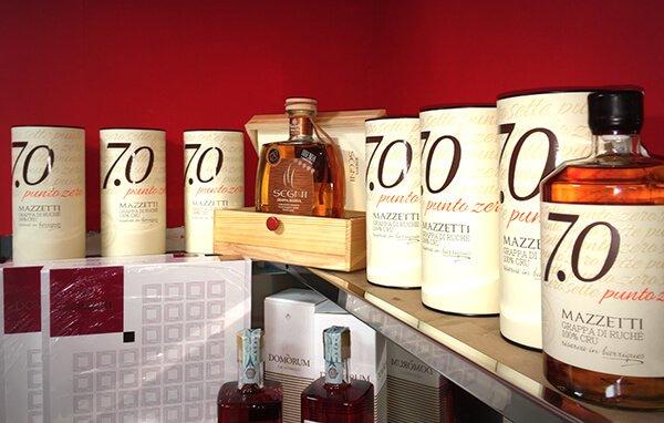 bottiglie di grappa di ruché Mazzetti in una scatola con accanto vari contenitori di bottiglie Mazzetti