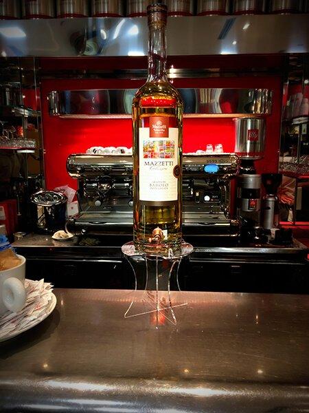 bottiglia di Grappa Mazzetti su un piedistallo posto su un bancone, con una macchina del caffè nello sfondo