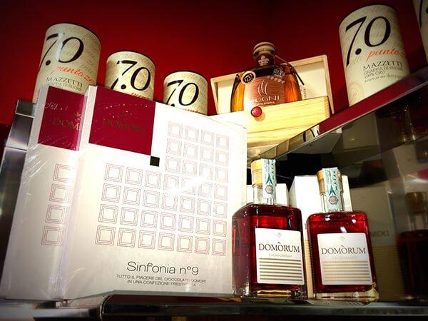 bottiglie di grappa al cioccolato Domorum con a fianco relativa scatola, mentre sopra c'è una bottiglia di grappa Segni e relativi contenitori