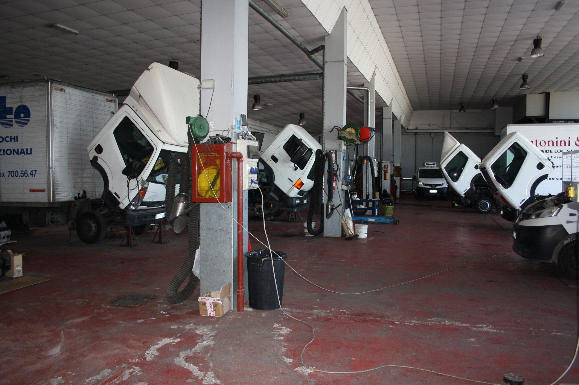 Veicoli industriali in riparazione dentro l'officina meccanica