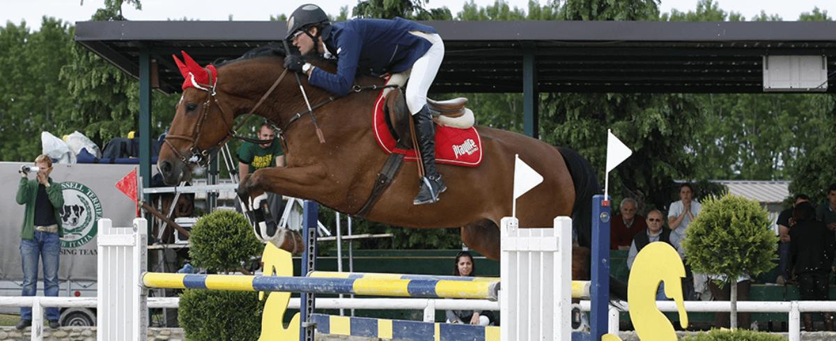 un uomo a cavallo salta un ostacolo