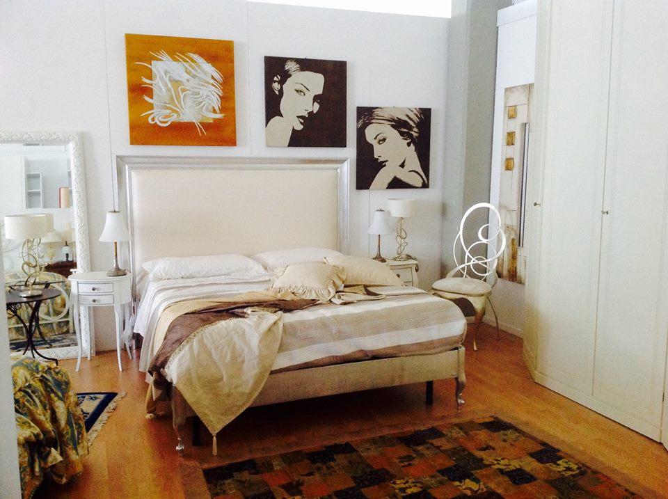 una camera da letto con un letto, sulla sinistra un armadio bianco, quadri al muro e altri oggetti