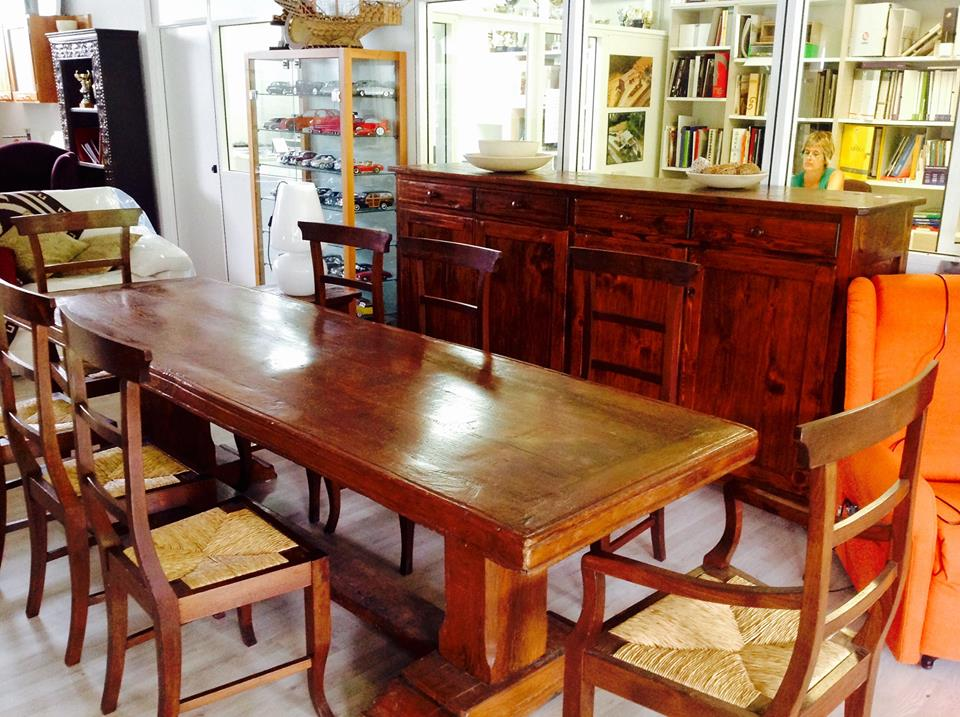 un tavolo  in legno con delle sedie e altri mobili in esposizione