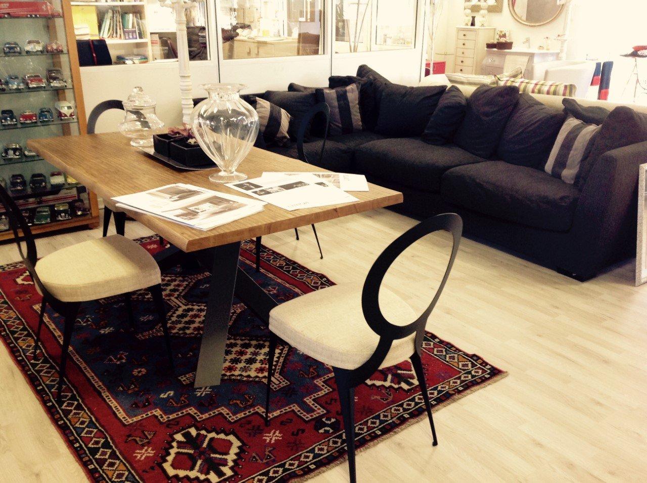una sala con un divano nero, un tavolo beige e delle sedie color panna con schienale nero