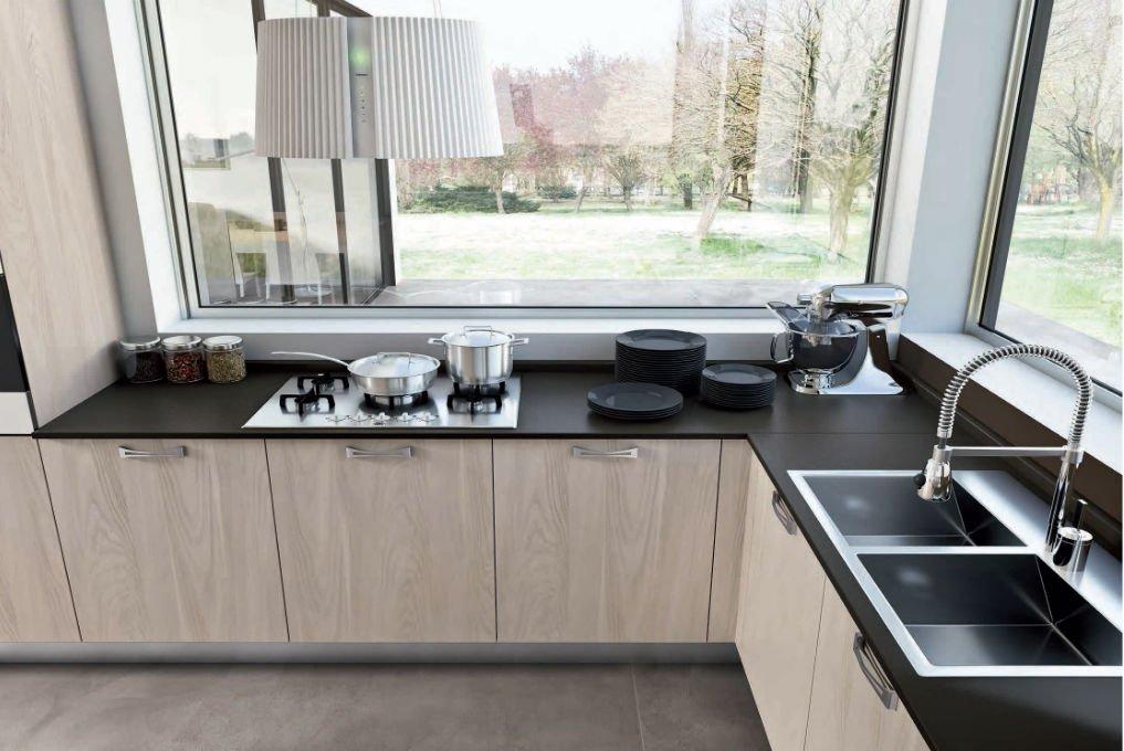 una cucina angolare con top nero e mobili beige